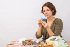 Mädchen, welches das Endstück den Spielzeugjungen hahn von einem dekorativen Band um die Tabelle mit Näharbeit antut lizenzfreie stockbilder