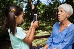 Mädchen, welches das Foto der Großmutter Zunge heraus haftend macht Lizenzfreie Stockbilder