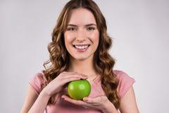 Mädchen, welches das grüne Apfellächeln hält lizenzfreie stockfotos
