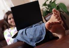 Mädchen, welches das Internet mit Füßen oben surft Lizenzfreie Stockfotos
