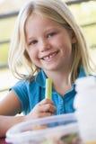 Mädchen, welches das Mittagessen am Kindergarten isst stockfotografie