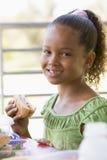 Mädchen, welches das Mittagessen am Kindergarten isst Lizenzfreies Stockfoto