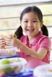 Mädchen, welches das Mittagessen am Kindergarten isst lizenzfreie stockfotos