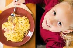 Mädchen, welches das Mittagessen oder Abendessen isst Stockfotografie