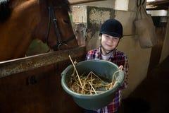 Mädchen, welches das Pferd im Stall einzieht lizenzfreie stockfotos