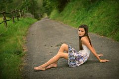 Mädchen, welches das Sitzen auf der Straße träumt Lizenzfreie Stockbilder
