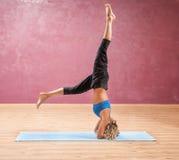 Mädchen, welches das Yoga steht auf Hauptumgedrehtem tut Lizenzfreie Stockfotos