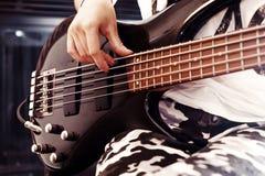 Mädchen, welches die Bass-Gitarre Innen in der Dunkelkammer spielt stockbild