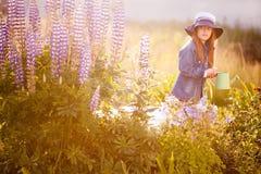 Mädchen, welches die Blumen wässert Lizenzfreies Stockfoto