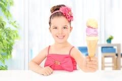 Mädchen, welches die Eiscreme sitzt im Wohnzimmer hält Stockbilder