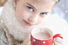 Mädchen, welches die heiße Schokolade im Freien trinkt Lizenzfreie Stockfotografie