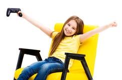 Mädchen, welches die Konsole, ein Spiel gewinnend hält stockfoto
