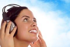 Mädchen, welches die Musik über der Sonne und dem blauen Himmel genießt stockfotos