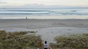Mädchen, welches die Sonnenuntergangansicht genießt und hinunter Treppe vor einem schönen Strand geht stock footage
