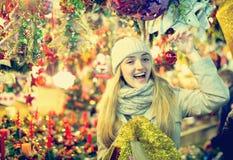 Mädchen, welches die Weihnachtsgeschenke im Freien wählt Stockbilder