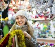 Mädchen, welches die Weihnachtsgeschenke im Freien wählt Stockfotografie
