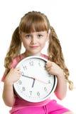 Mädchen, welches die Zeit mit sieben Uhr im Studio anzeigt Stockbilder