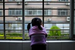 Mädchen, welches heraus das Fenster schaut Stockfotografie