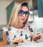 Mädchen, welches zu Hause das Schreiben in ein Papiernotizbuch sitzt Stockbild