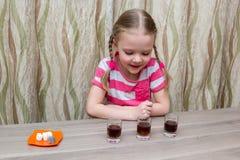 Mädchen wendet chemische Erfahrung bei Tisch zu Hause auf Lizenzfreie Stockbilder