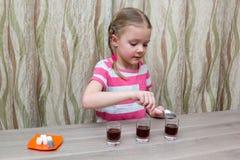 Mädchen wendet chemische Erfahrung bei Tisch zu Hause auf Stockfotos