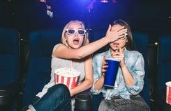 Mädchen werden erschrocken Sie passen einen Horrorfilm auf Blondes Mädchen bedeckt Augen ihres Freunds Brunette versucht zu lizenzfreie stockfotografie