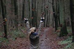 Mädchen wirft Blätter im Wald Lizenzfreie Stockbilder