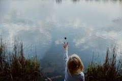 Mädchen wirft einen Kiefernkegel in den See Stockbild