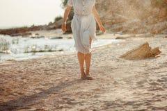 Mädchen wirft Sand am Strand lizenzfreie stockbilder