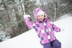 Mädchen wirft Schnee Stockfoto