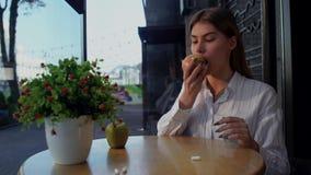 Mädchen wirft Vitaminpillen mit der Hand von der Tabelle und vom Essen eines grünen köstlichen Apfels ab, der auf der Terrasse vo stock video