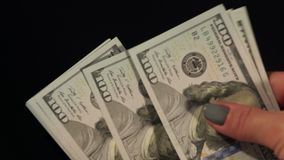Mädchen zählt Geld auf einem schwarzen Hintergrund, Nahaufnahme stock video