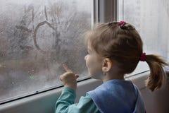 Mädchen zeichnet auf Glas lizenzfreie stockfotografie