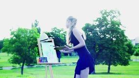Mädchen zeichnet auf plein grünes Gras und Baum im Park stock footage