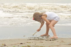 Mädchen zeichnet in den Sand auf der Küste Lizenzfreie Stockfotos