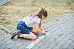 Mädchen zeichnet durch eine Kreide auf Asphalt lizenzfreie stockfotos