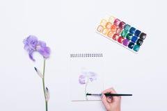 Mädchen zeichnet eine blaue Blume in einem Notizbuch mit Aquarellen Lizenzfreies Stockfoto
