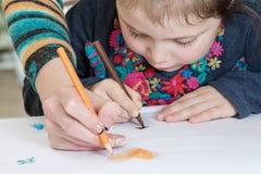 Mädchen zeichnet mit Mutter Stockfoto