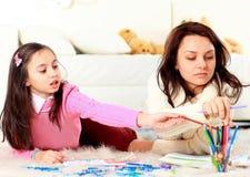 Mädchen zeichnet mit seiner Mutter Stockbild