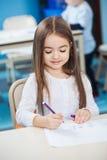 Mädchen-Zeichnung mit Skizze Pen At Desk Lizenzfreie Stockfotos