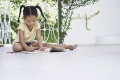 Mädchen-Zeichnung mit Zeichenstiften auf Portal Stockfotos