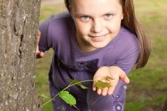Mädchen zeigt grünen Eintragfaden des Baums Stockfotografie