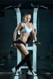 Mädchen zeigt ihr schöne Muskeln nahe der Maschine für Bodybuilder Stockbilder