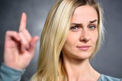 Mädchen zeigt sich einen Zeigefinger und drückt ein Zeichen der Aufmerksamkeit aus stockfoto