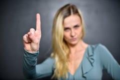 Mädchen zeigt sich einen Zeigefinger und drückt ein Zeichen der Aufmerksamkeit aus lizenzfreies stockbild