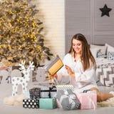 Mädchen zu Hause auf dem Weihnachten, das Geschenke unter einem Weihnachten-tre betrachtet stockbilder