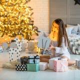 Mädchen zu Hause auf dem Weihnachten, das Geschenke unter einem Weihnachten-tre betrachtet stockfotos