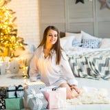 Mädchen zu Hause auf dem Weihnachten, das Geschenke unter einem Weihnachten-tre betrachtet stockfotografie