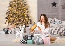 Mädchen zu Hause auf dem Weihnachten, das Geschenke unter einem Weihnachten-tre betrachtet lizenzfreies stockfoto