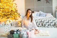 Mädchen zu Hause auf dem Weihnachten, das Geschenke unter einem Weihnachten-tre betrachtet stockbild